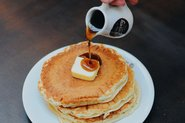 Hand pouring syrup over pancakes; Photo by Pexels, Matheus Gomes