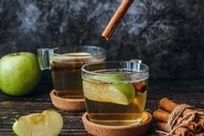 Green apples and cinnamon sticks falling into two cups of apple tea; Photo by Pexels, Tijana Drndarski